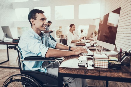 Man on Wheelchair Working on Computer in Office. Disabled Young Man. Man on Wheelchair. Recovery and Healthcare Concepts. Teamwork in Office. Young Worker. Sitting Man. Man with Computer.