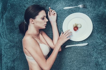 Slim Girl with Anorexia Lying on Sofa with Plate. Sliced Vegetables. Woman with Anorexia. Weigth Problem Concept. Tomato and Cucumber. Woman in Bra. Girl on Diet. Woman on Gray Sofa.