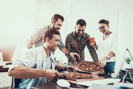 Young People Have Lunch with Pizza in Office. Teamwork in Office. Young Worker. Sitting Man. Box with Pizza. Young Girl in Glasses. Young Worker. Manager on Break. Man on Wheelchair.