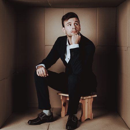 Young Businessman in Black Suit in Cardboard Box. Young Man in Suit. Life in Little Cardboard Box. Uncomfortable Life. Personal Spase Concept. Uncomfortable House Concept. Young Introvert. Imagens