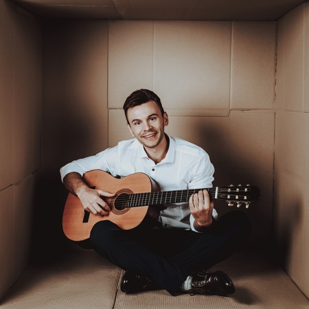 Young Man in Shirt Playing Guitar in Cardboard Box. Young Man in White Shirt. Life in Little Cardboard Box. Uncomfortable Life. Personal Spase Concepts. Young Introvert.