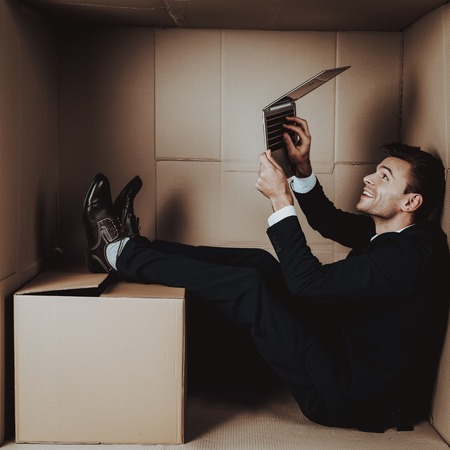 Young Businessman with Laptop in Cardboard Box. Young Man in Suit. Life in Little Cardboard Box. Uncomfortable Life. Personal Spase Concepts. Using Digital Device. Young Introvert. Standard-Bild