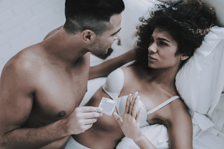 Young Beautiful Couple in Underwear Lying on Bed. Handsome Man holding Condom. Attractive Woman Refusing Use Contraception. Passionate Romantic Couple about to have Sex at Home. Intimate Relationship