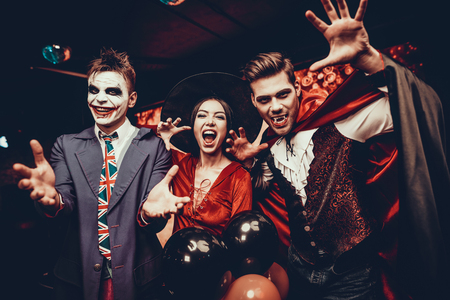 Young People in Costumes Celebrating Halloween. Group of Young Happy Friends Wearing Halloween Costumes having Fun at Party in Nightclub by doing Scary faces. Celebration of Halloween Stock Photo