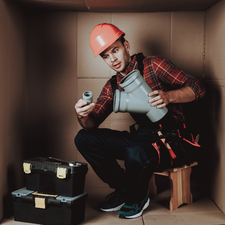 Worker in Orange Helmet Sitting in Cardboard Box. Young Man in Uniform. Uncomfortable Life. Personal Spase Concept. Uncomfortable House Concept. Young Introvert. Worker with Tools. Stock Photo