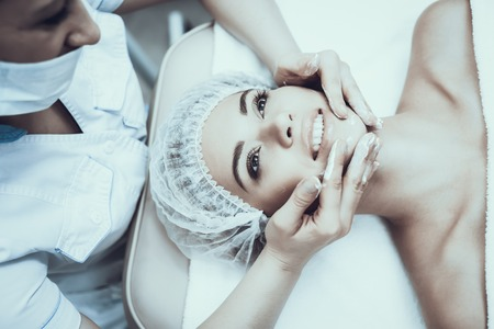 Young Woman in Spa Salon for Cleansing Massage. Girl in Beauty Salon. Modern Cosmetology. Proffesional Cosmetologist. Doctor in White Coat. Womens Beauty Concept. Skin Care and Cleaning.