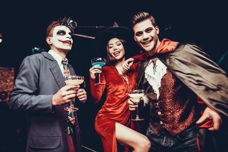 Jóvenes felices en disfraces en la fiesta de Halloween. Grupo de jóvenes amigos sonrientes con disfraces de Halloween bebiendo cócteles y divirtiéndose en la discoteca. Celebración de Halloween Foto de archivo