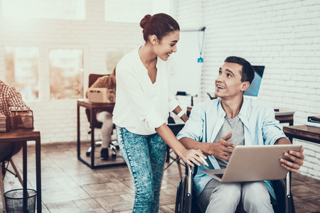 Woman near Man on Wheelchair with Tablet in Office. Smiling Woman. Disabled Young Man. Man on Wheelchair. Recovery and Healthcare Concepts. Teamwork in Office. Young Worker. Sitting Man.