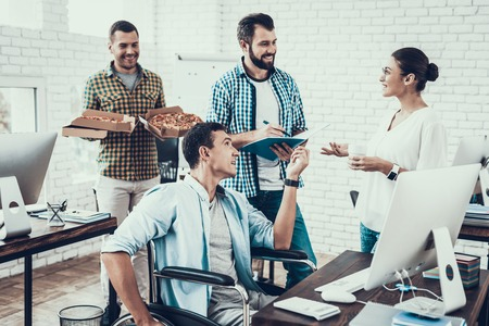 Young People Have Lunch with Pizza in Office. Teamwork in Office. Young Worker. Sitting Man. Box with Pizza. Young Girl in Glasses. Young Worker. Manager on Break. Man on Wheelchair. Imagens - 109792861