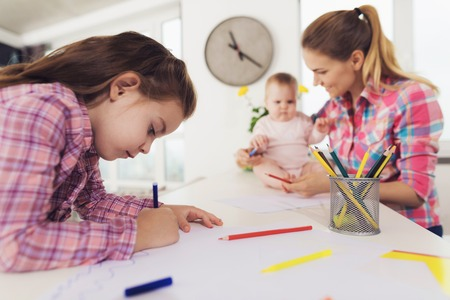 Happy Family Painting with Pencils Indoors. Cute Pretty Child Drawing on Paper with Colored Pencils at White Table. Young Mom Helping Baby with Pencil. Children Activity Concept Archivio Fotografico - 109878584