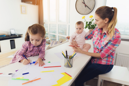 Girl Painting with Mother and Younger Sister. Cute Pretty Child Drawing on Paper with Colored Pencils at White Table. Younger Baby Looking at Sisters Picture. Children Activity Concept Stock Photo