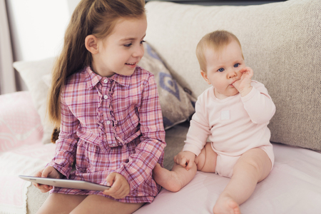 Girl Use Tablet and Sit with Young Sister Indoors. Older Long-Haired Girl Holding Pad in Hands Looking at Cute Baby Keeping Finger in Mouth while Resting on Comfortable Couch at Home.