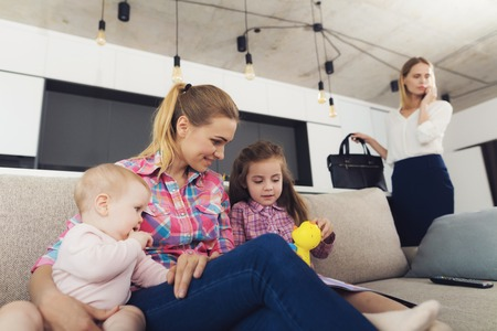 Babysitter Looks After Kids while Mom Telephones. Young Nanny Wearing Casual Clothes Sitting on Couch and Playing with Kids. Businesswoman Talking Phone in Bright Living Room Stock Photo