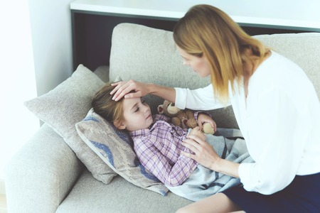 Attentive Mother Sits Near Sick Little Daughter. Pretty Ill Girl has Cold Lying on Sofa under Blanket or Plaid. Careful Mom Caressing Child Head and Checking Kids Temperature Imagens