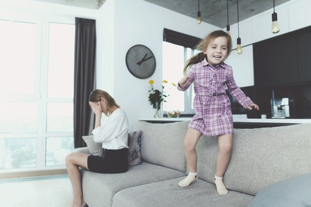 Girl Having Fun Jumping on Sofa when Mother Upset. Cheerful Child Messing Around on Big Comfortable Couch in Bright Modern Living Room. Mom Feels Disappointed Holding Head