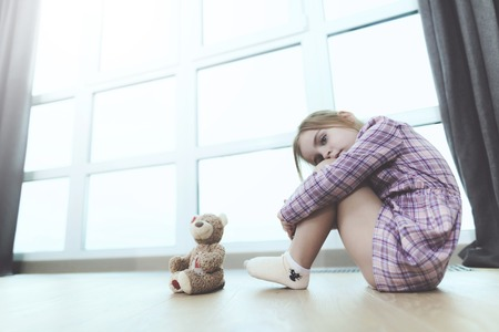 Sad Girl Sit with Teddy Bear on Floor Indoors. Upset Pretty Caucasian Child Wearing Casual Clothes Sitting with Clenched Knees Near Large Panoramic Window Looking at Camera. Childhood Concept