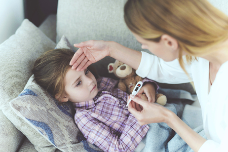 Careful Mother Checking Sick Child Temperature. Attentive Woman Sits Near Ill Little Daughter. Pretty Girl has Cold and Fever Lying on Sofa under Blanket or Plaid. Careful Mom Holding Thermometer Stok Fotoğraf
