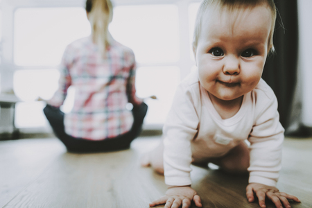 Cute Smiling Baby Crawls and Mother Sitting Back near Window. Portrait of Sweet Beautiful Caucasian Child Playing on Floor in Modern Living Room and Young Mom Wears Casual Clothes. Childhood concept