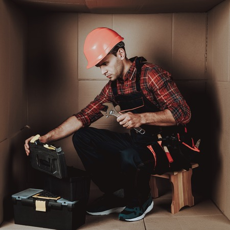 Worker in Orange Helmet Sitting in Cardboard Box. Young Man in Uniform.