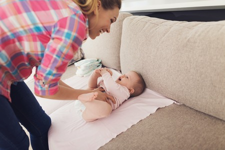 Careful Mother Swaddles Smiling Baby on Couch