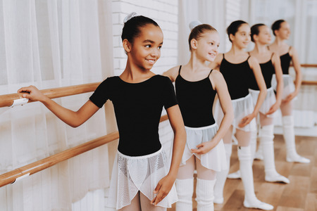 Ballet Training of Group of Young Girls Indoors. Classical Ballet. Girl in Balerina Tutu. Training Indoor. Cute Dancers. Performance in Hall. Dancing Practice. Girls in White Dresses.