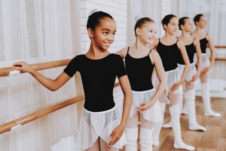 Ballett-Training der Gruppe junger Mädchen drinnen. Klassisches Ballett. Mädchen im Balerina-Tutu. Indoor-Training. Nette Tänzer. Aufführung in Halle. Tanzpraxis. Mädchen in weißen Kleidern.