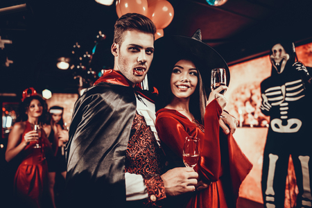 Young Happy Couple in Costumes at Halloween Party. Handsome Man and Beautiful Woman Drinking Champagne at Halloween Party in Nightclub. Friends having Fun. Celebration of Halloween Standard-Bild