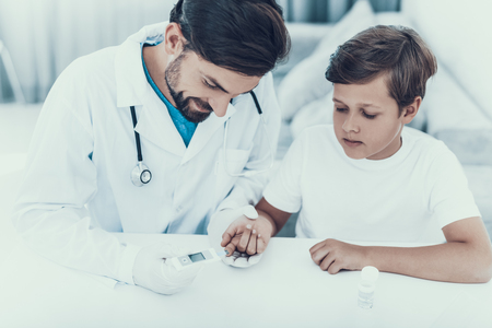 Doctor Taking Blood Sample from Boys Finger. Diabetes Concept. Sugar in Blood. Healthcare Concept. Young Man in Uniform. White Coat. Medical Equipment. Boy in Clinic. Glucometer in Hand.
