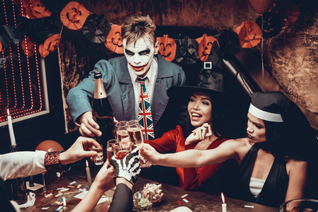 Young Smiling People in Costumes Clinking Glasses. Group of Young Happy People Wearing Costumes at Halloween Party Sitting at Table and Drinking Champagne. Celebration of Halloween