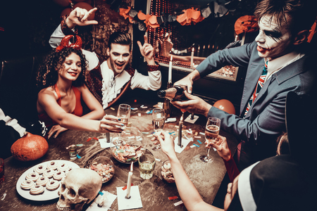 Young People Wearing Costumes Drinking Champagne. Group of Young Happy People in Costumes at Halloween Party Sitting at Table and Drinking Champagne. Young Man Pouring Champagne