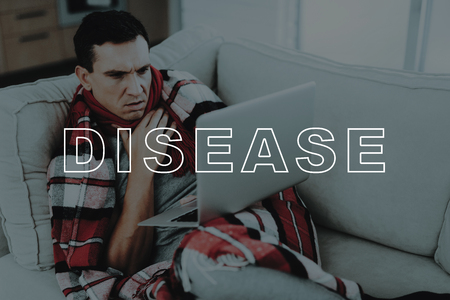 Man With Cold Is Sitting On Couch With A Laptop.