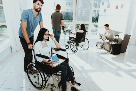 People in Wheelchair. Disabled in Hall. Woman in Wheelchair. Man on Crutches. Group Disabled People. Room with Panoramic View. Gray Sofa. White Interior. Limited Opportunities. Disabled in Room. Stock Photo