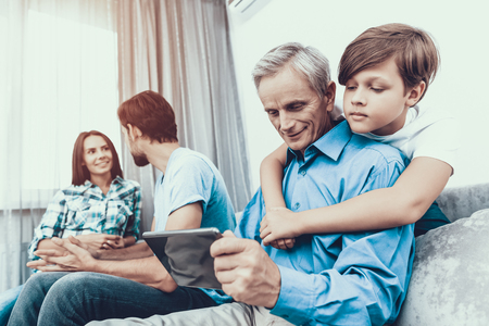 Happy Family Using Tablet PC Together at Home. Using Digital Device. Spending Time Together at Home. Father and Son. Smiling People. Have Fun Indoor. Parenthood Concept. Family at Home. 版權商用圖片