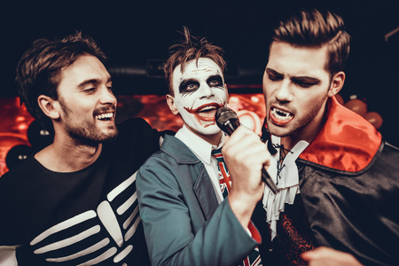Young Men in Halloween Costumes Singing Karaoke. Happy Smiling Friends Wearing Costumes having Fun by Singing with Microphone at Halloween Party in Nightclub. Celebration of Halloween