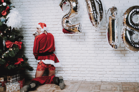 Drunk Santa Claus near New Year Tree after Party. Christmas Tree in Office. Celebrating of New Year. Red Costume. Man in Red Cap. Drank Man. Red Pants. Alkoholic near Christmas Tree.