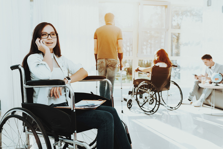 Person in Wheelchair. Disabled in Hall. Woman in Wheelchair. Man on Crutches. Man in Wheelchair. Room with Panoramic View. Gray Sofa. White Interior. Speaks by Phone Disabled. Limited Opportunities.