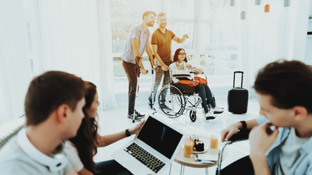 People in Wheelchair. Disabled in Hall. Woman in Wheelchair. Man on Crutches. Disabled Hall Airport. Room with Panoramic View. Gray Sofa. White Interior. Limited Opportunities. Healthy Passengers. Imagens