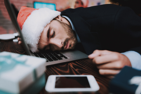 Tired Young Businessman in Office on New Year Eve. Christmas Tree in Office. Laptop on Desk. Business Concept. Man in Black Suit. Celebrating of New Year. Using Digital Device. Young Man. Stock Photo
