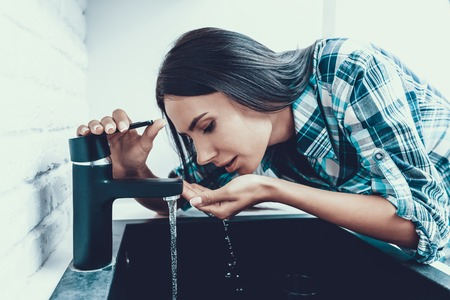 Jonge vrouw in Shirt Drinkwater in de keuken. Gezondheidszorgconcept. Zoetwater. Jonge vrouw. Vrouw in overhemd. Meisje in Kitcken. Gezond Drankconcept. Tik in Keuken. Vrouw thuis.
