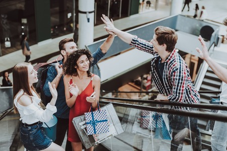 Friends Met on Escalator in Mall on Shopping. Shopping Concept. Girl in Red Dress. Unshaved Young Man. Holding Packages. Pack from Mall in Hands. Greeting to Friends. Escalator in Modern Market. Banco de Imagens