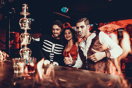 People in Costumes Looking at Flaming Cocktail. Group of Smiling Young Friends Wearing Costumes Excited about Flaming Cocktails on Bar counter in Nightclub. Celebration of Halloween