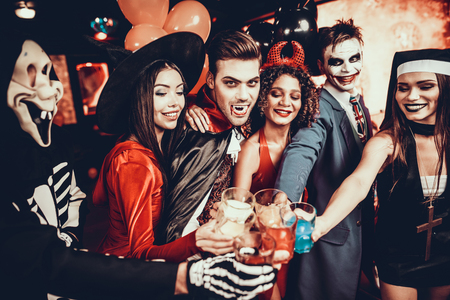 Friends in Halloween Costumes Drinking Cocktails. Group of Young Happy People Wearing Costumes at Halloween Party Drinking Cocktails and having Fun in Nightclub. Celebration of Halloween Stock Photo