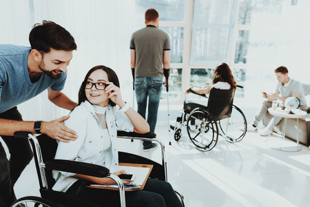 Girl in Wheelchair. Disabled in Hall. Woman in Wheelchair. Man on Crutches. Man in Wheelchair. Room with Panoramic View. Gray Sofa. White Interior. Limited Opportunities. Man Hug Girl. Woman Disabled.