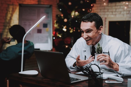 Young Doctor in Uniform in Office on New Year Eve. Christmas Tree in Office. Computer on Desk. Man with Cactusin Vase. Man in White Coat. Celebrating of New Year. Using Digital Device.