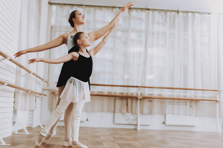 Ballet Training of Little Girl with Teacher Indoor. Classical Ballet. Girl in Balerina Tutu. Training Indoor. Cute Dancers. Performance in Hall. Dancing Practice. Girl in White Dresses. Foto de archivo - 110175307