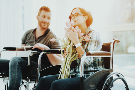 People in Wheelchair. Woman Disabled with Flowers. Panoramic View. White Interior. Romantic Meeting Disabled. Loving Disabled. People with Limited Opportunities. Gives Gift. Sniffing Flowers. Imagens