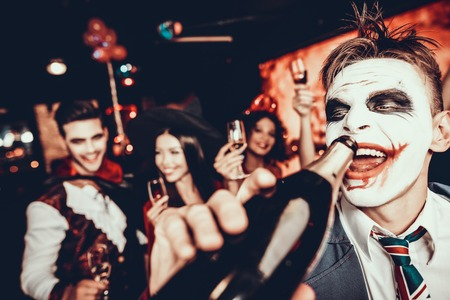 Young Man in Halloween Costume Drinking Champagne. Portrait of Young Man Wearing Costume Drinking Champagne out of Bottle at Halloween Party in Nightclub. Celebration of Halloween
