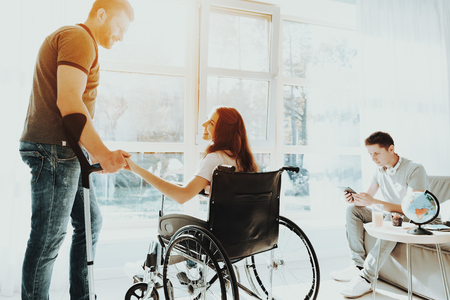 Woman Hold Hand Man. People in Wheelchair. Disabled in Hall. Woman in Wheelchair. Man on Crutches. Man in Wheelchair. Room with Panoramic View. Gray Sofa. White Interior. Limited Opportunities.