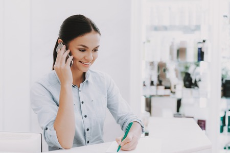 Woman Receptionist. Receptionist in Workplace. Workplace in Beauty Salon. White Interior. White Reception Desk. Beauty Consept. Smiling Salon Employee. Customer Registration. Receptionist Speaks Phone Stock Photo