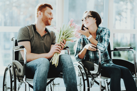 People in Wheelchair. Man with Flowers. Disabled Hall Airport. Panoramic View. White Interior. Romantic Meeting Disabled. Loving Disabled. People with Limited Opportunities. Gives Gift. Give Flowers.